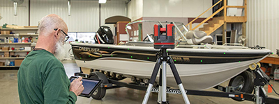 man laser measuring a boat for a canvas cover